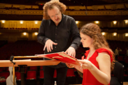 SLSO Music Director Stephane Deneve and harpist Allegra Lilly look at a music score together during rehearsal