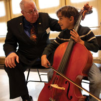 Young boy with cello and Symphony Volunteer